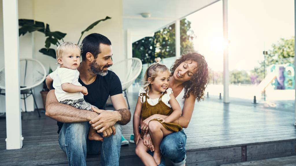 Modern mother and father with two children at home on veranda