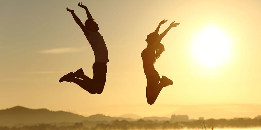 Silhouettes of a man and woman in active wear jumping up with arms raised