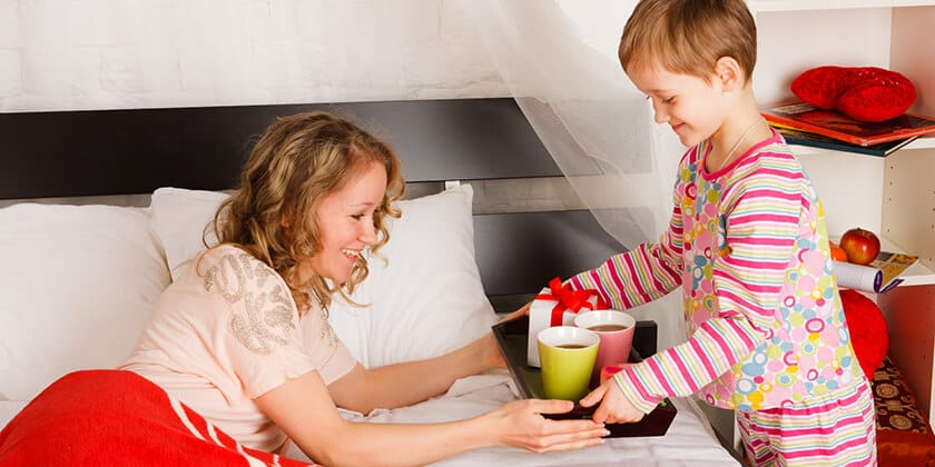 child bringing mother breakfast in bed