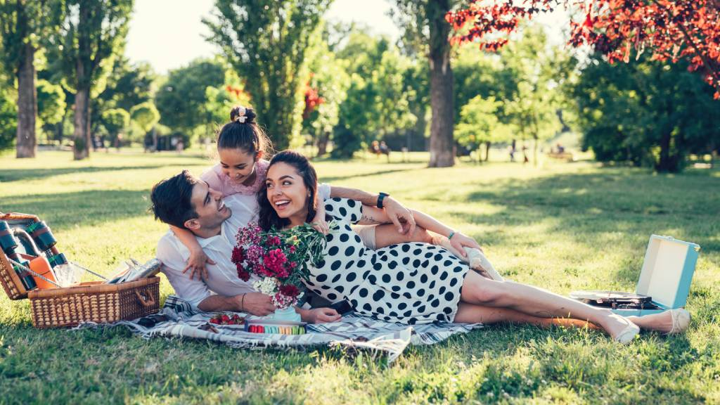 Family of three in the park with Valentine's Day roses and picnic