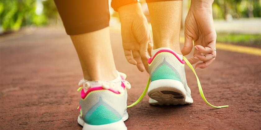 woman tying shoelaces while running