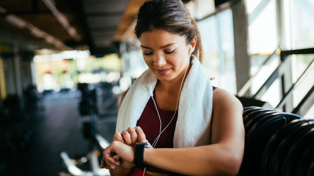 Woman in active wear checking her interval training time on smartwatch