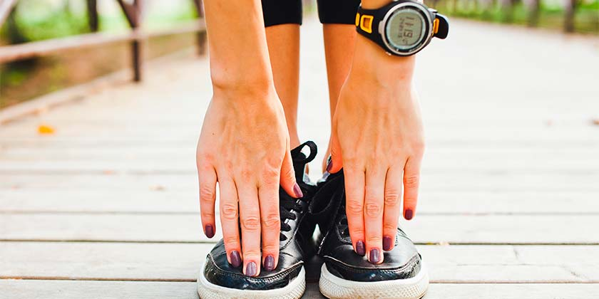 Woman's hands stretching down to her shoes wearing running sneakers