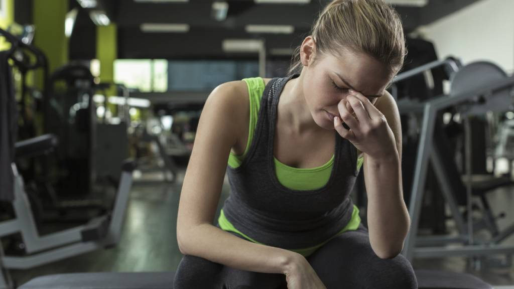 Woman in a gym with a headache after workout