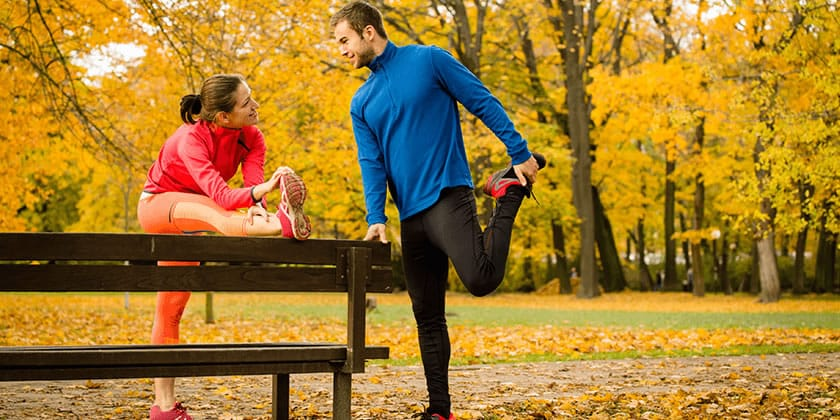 man and woman running and stretching outdoors