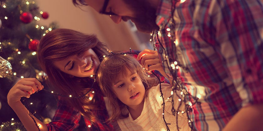 parents putting up christmas lights with child