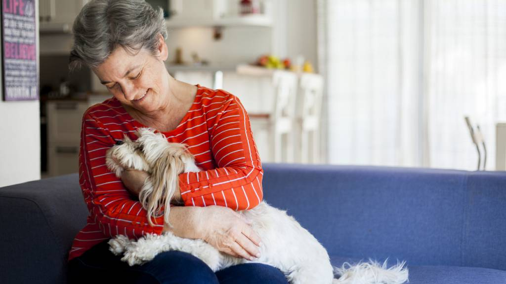 older woman comforting dog