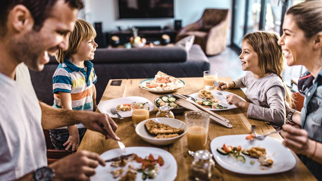 Family of four at dinner table enjoying a meal