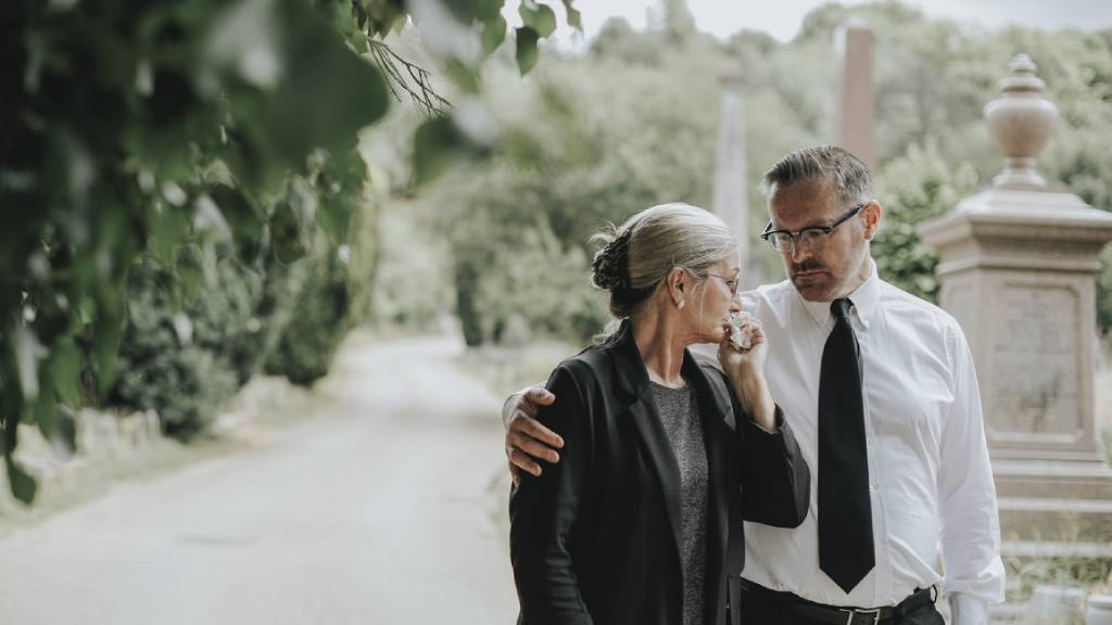 man comforting woman at funeral