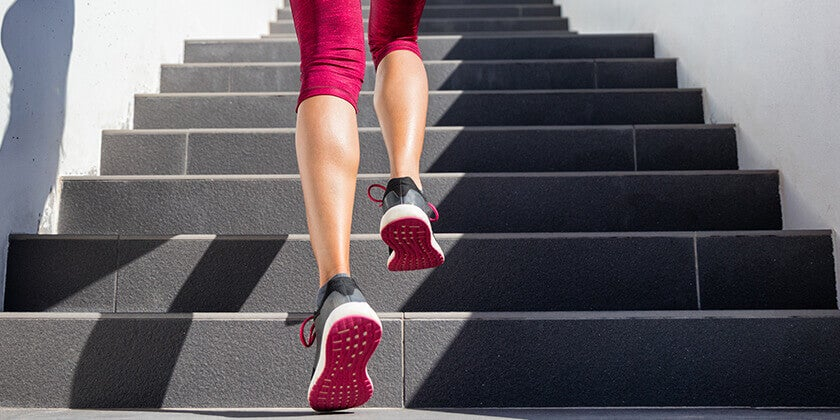Woman in red tights running up set of grey stairs