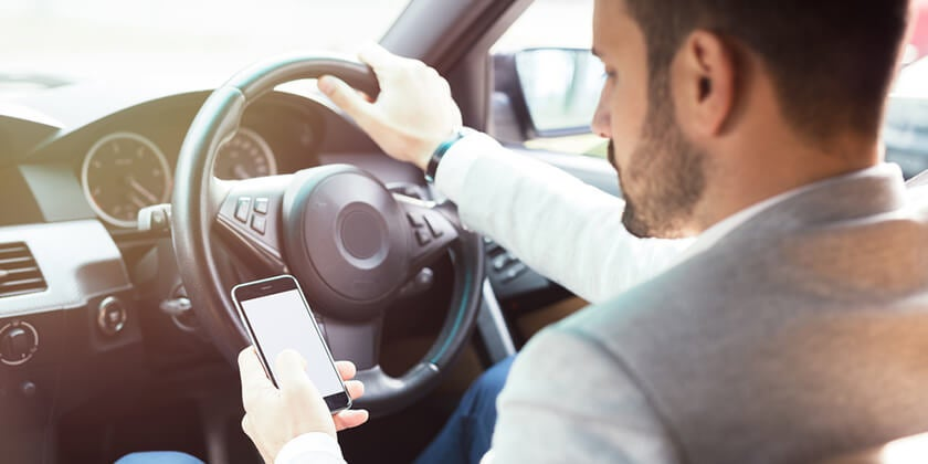 driver illegally using phone in car, illustrating penalty offences