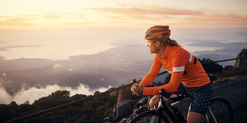 woman cycling on high roads with mountain view