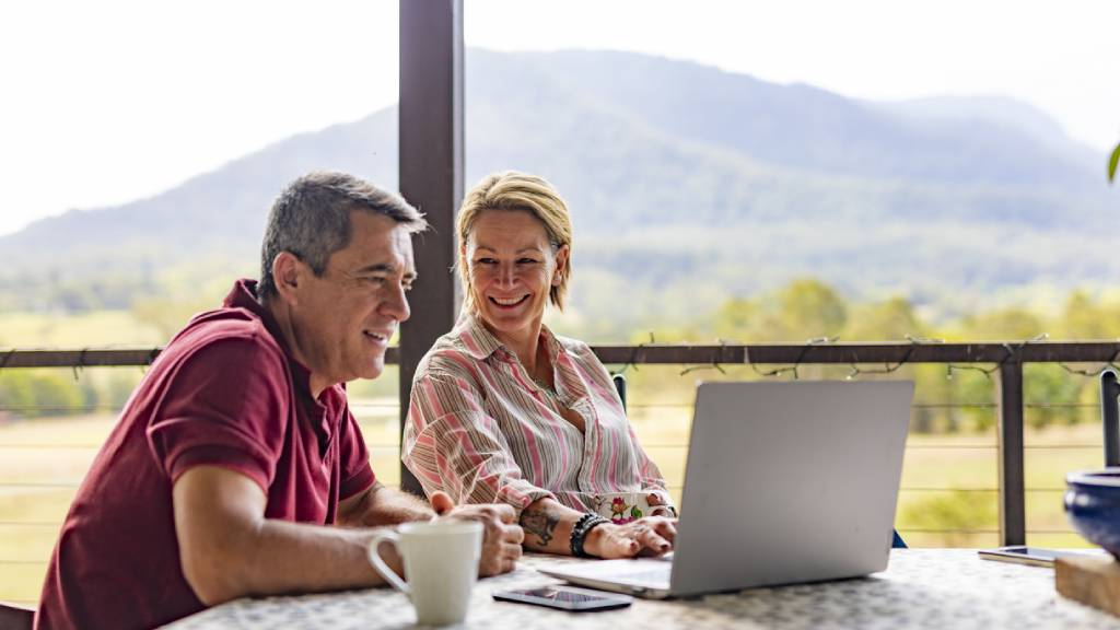 mid aged couple talking about life insurance using laptop