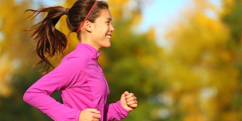 Woman running in purple tracksuit top with brown hair in ponytail
