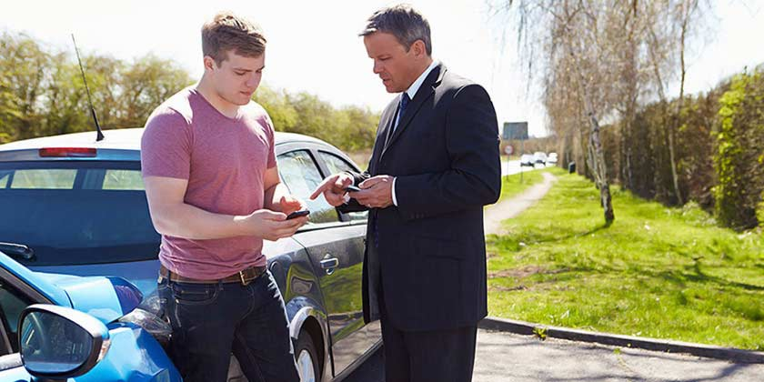 two men at accident scene exchanging details