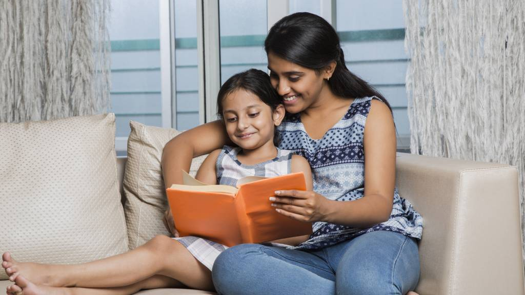 Mother and daughter reading a book at home on the couch