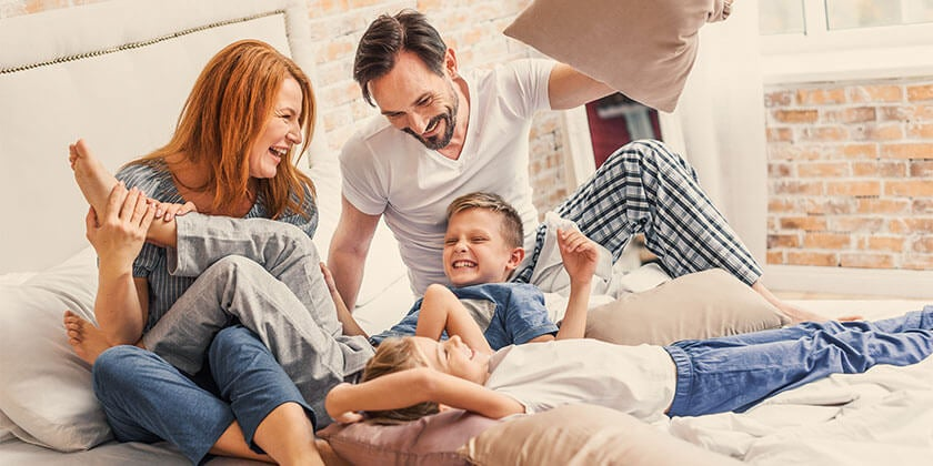 young family playing on bed