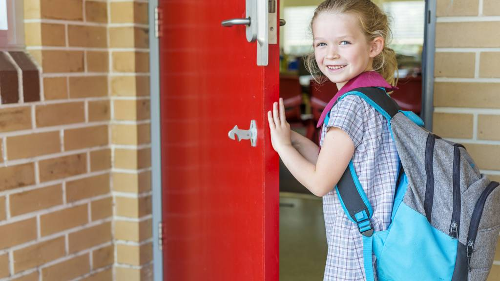 Child on first day of school in uniform near school door