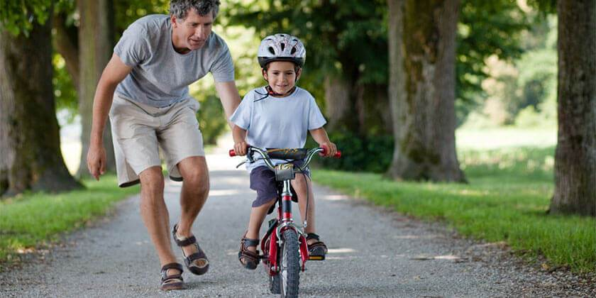 dad pushing child on bike