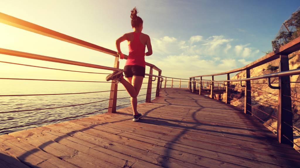 Woman jogging along a beachside boardwalk