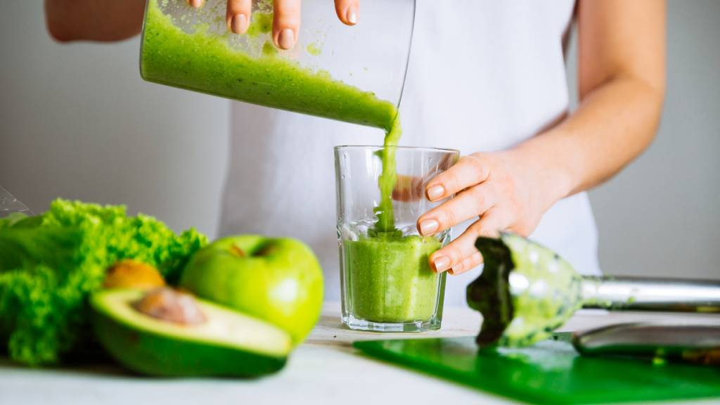 Woman pouring a glass of green juice