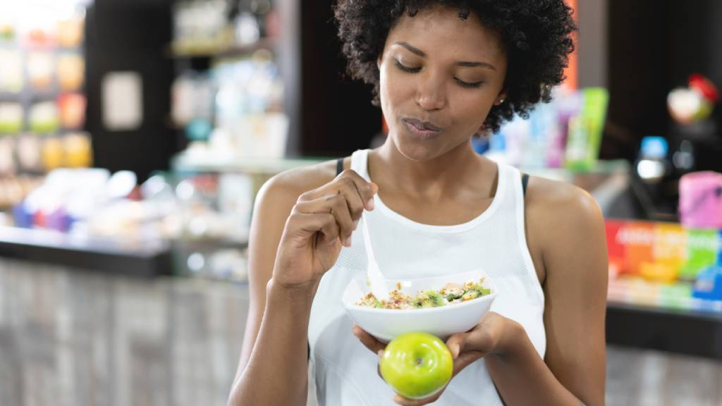 Woman in white singlet eating bowl of muesli holding a green apple