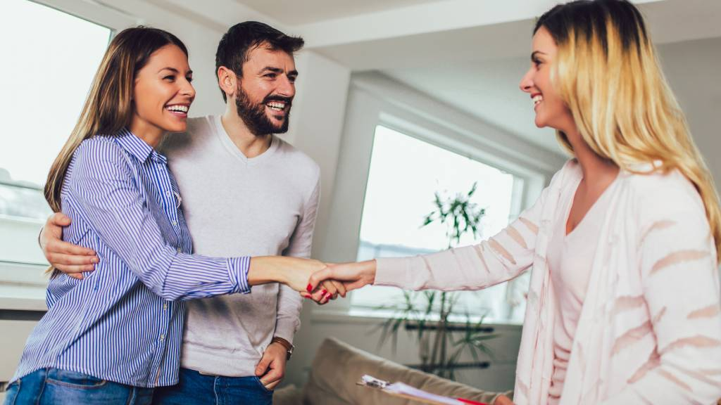 Couple shaking hands with a realtor, buying a home