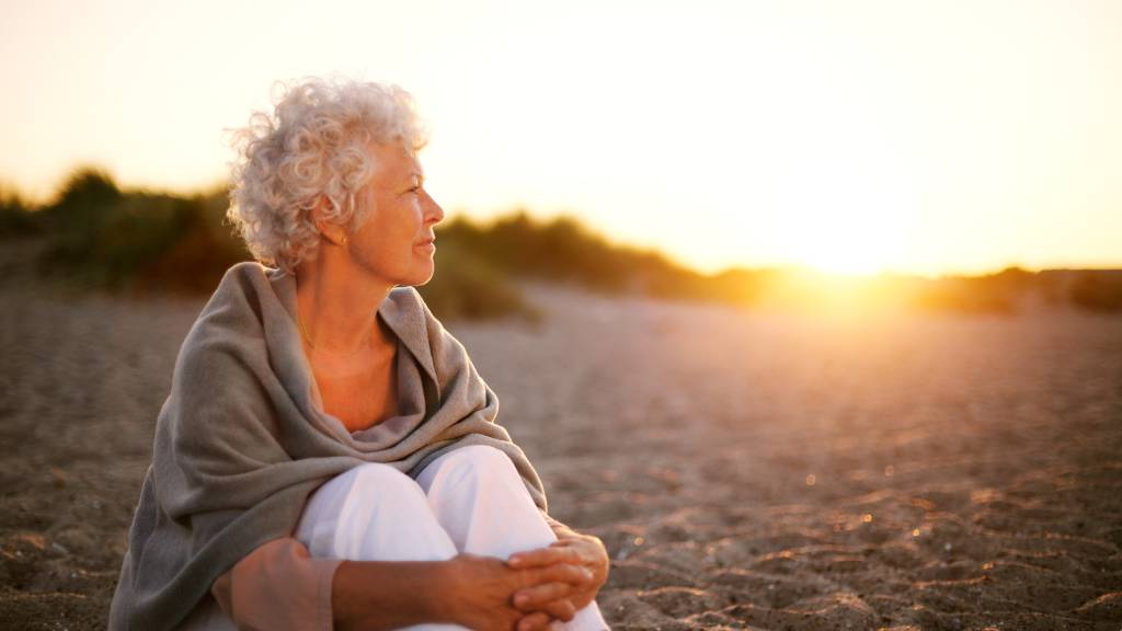 Mature woman on beach looking into horizon