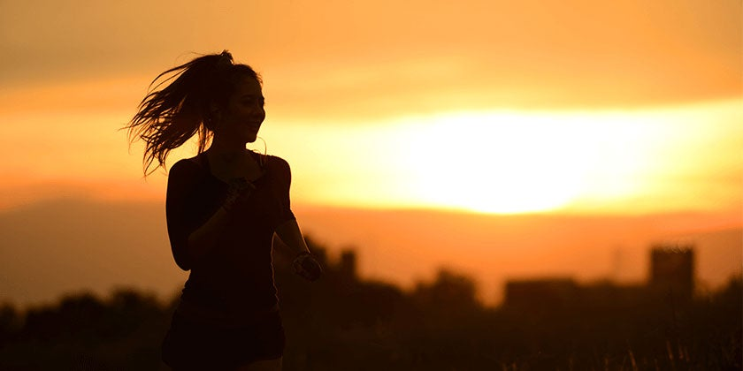 Silhouette of a woman running at sunset