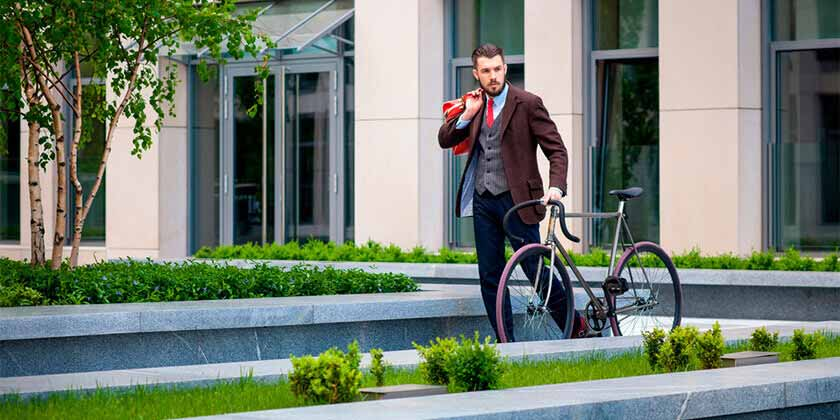 Man in office wear holding a red bag and walking with a bicycle in green office garden