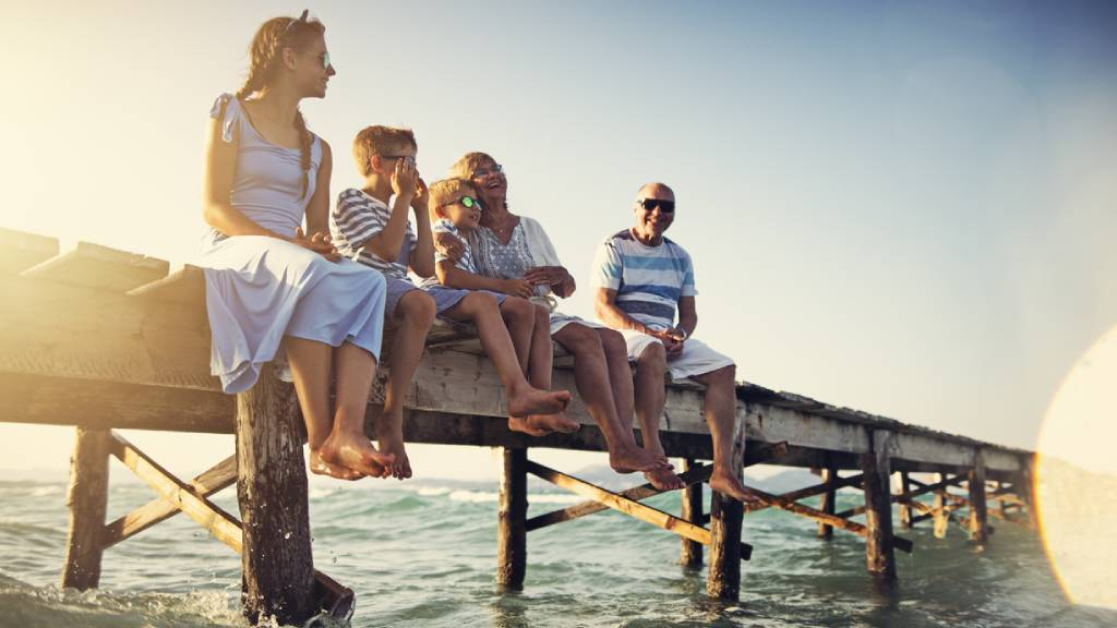 happy family with children sitting on pier