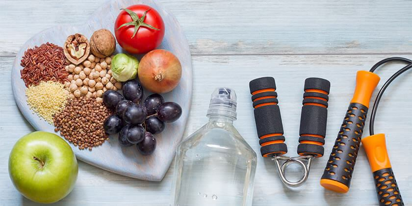 Healthy fruit and grains on heart shaped cutting board with water bottle, apple and fitness equipment