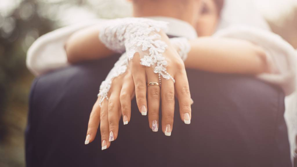 Bride and groom on wedding day - detail of fingers and rings