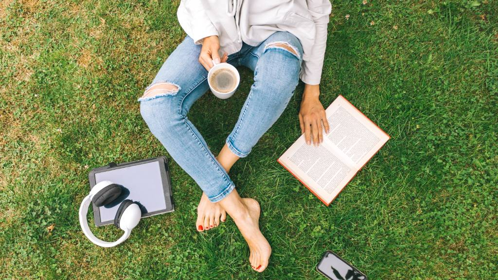 Young woman sitting on the grass drinking coffee and reading a book