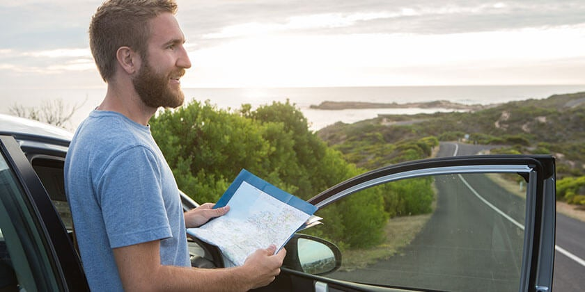 man travelling in car with map