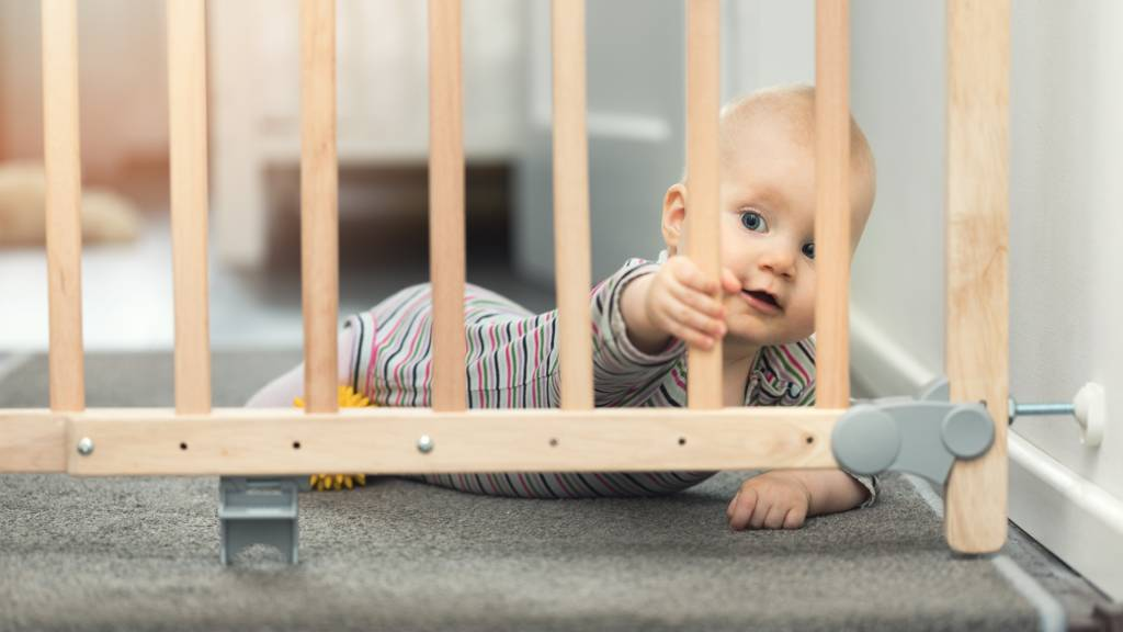 Small baby in onesie shown behind baby gate