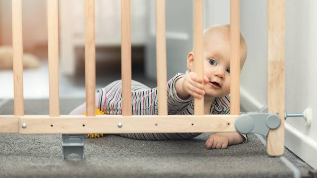 Small baby in onesie shown behind baby gate