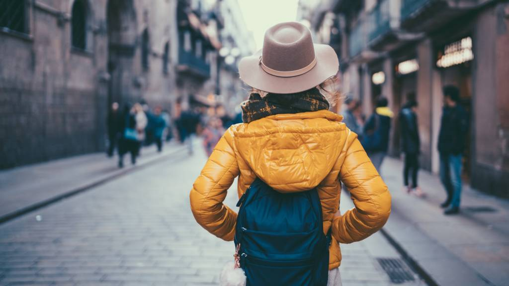 Woman traveller with a backpack and yellow puffer jacket
