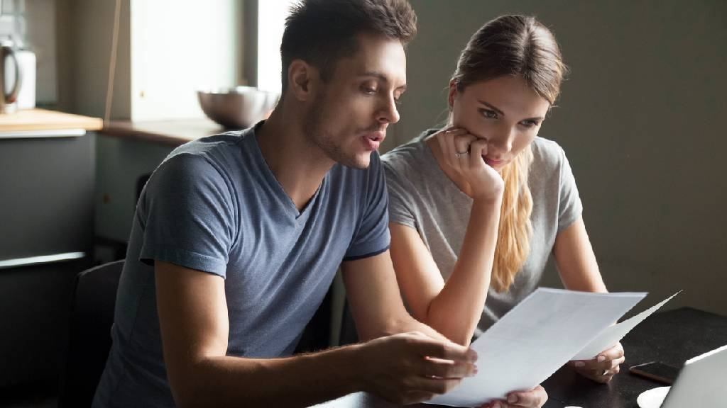 young couple discussing life insurance and looking at paperwork