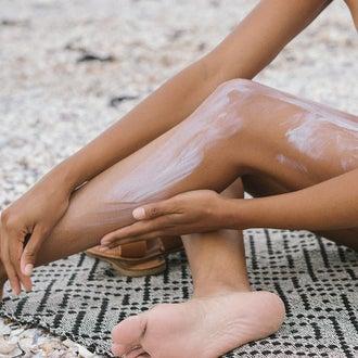 Woman putting sunscreen on legs