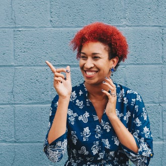 Lady with red hair smiling and pointing to the side