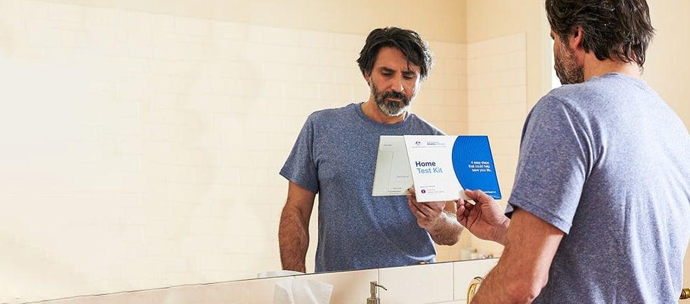 Bowel Cancer Screening | Man holding bowel cancer home test kit near bathroom sink