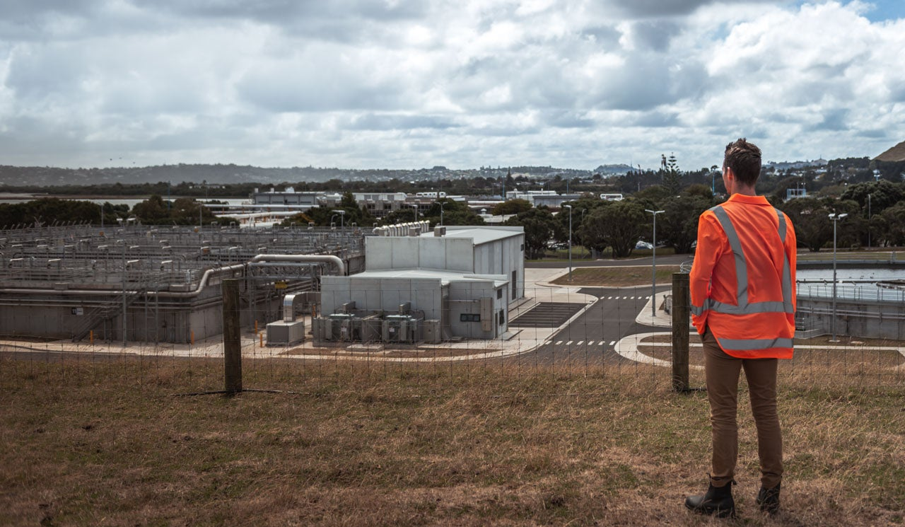 Watercare's Environmental Scientist Liam Templeton takes in a view of the large infrastructure outdoors at the Māngere Wastewater Treatment Plant.