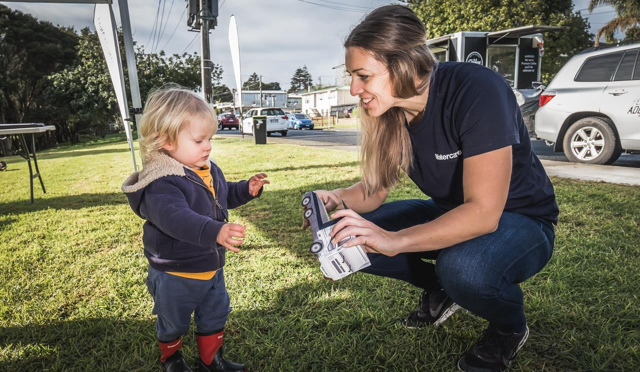 Stakeholder liaison advisor, Jennifer Charteris shares a toy truck and a moment, with a young resident at an infrastructure project information day.