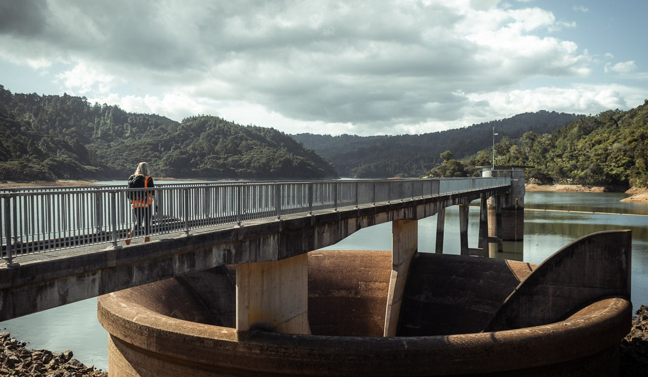 Watercare hydrologist Florence Mills walks along dam towards measurement and gauge positions.
