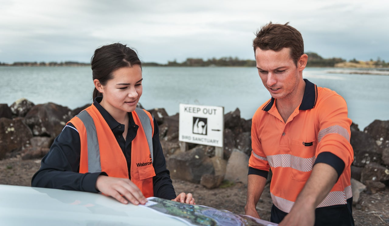 Watercare's Environmental Scientist Liam Templeton and his colleague Jen Harbour review maps of the bird sanctuaries in the background in Manukau Harbour.