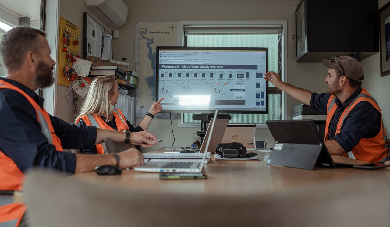 Watercare hydrologists and dam technicians conduct a weekly catch up at their Lower Huia dam office, discussing flow rates and water supply levels displayed on screens.