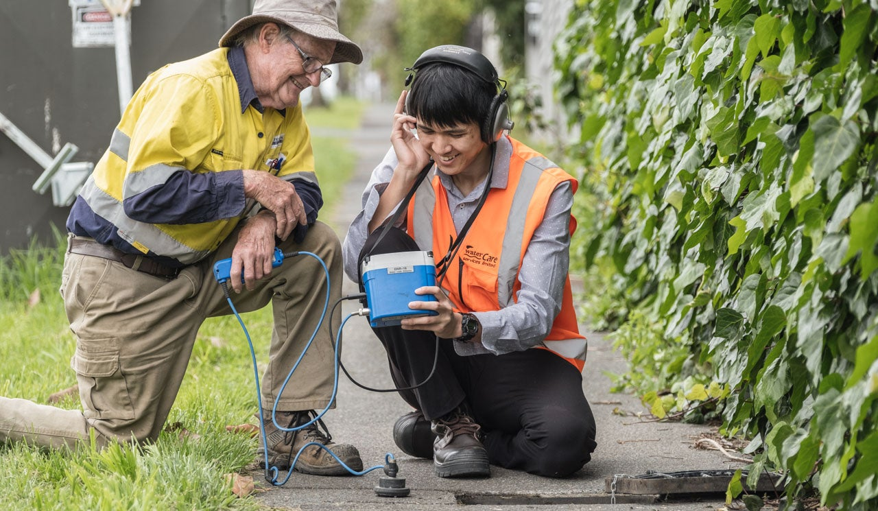 Watercare staff using audio equipment to sonically detect underground leaks.