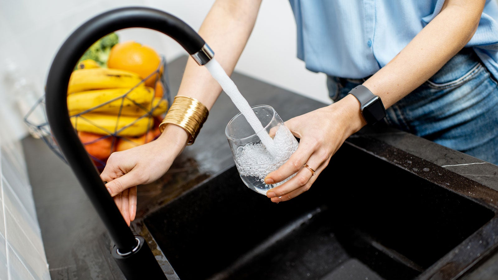Person filling a glass of water at the kitchen sink.