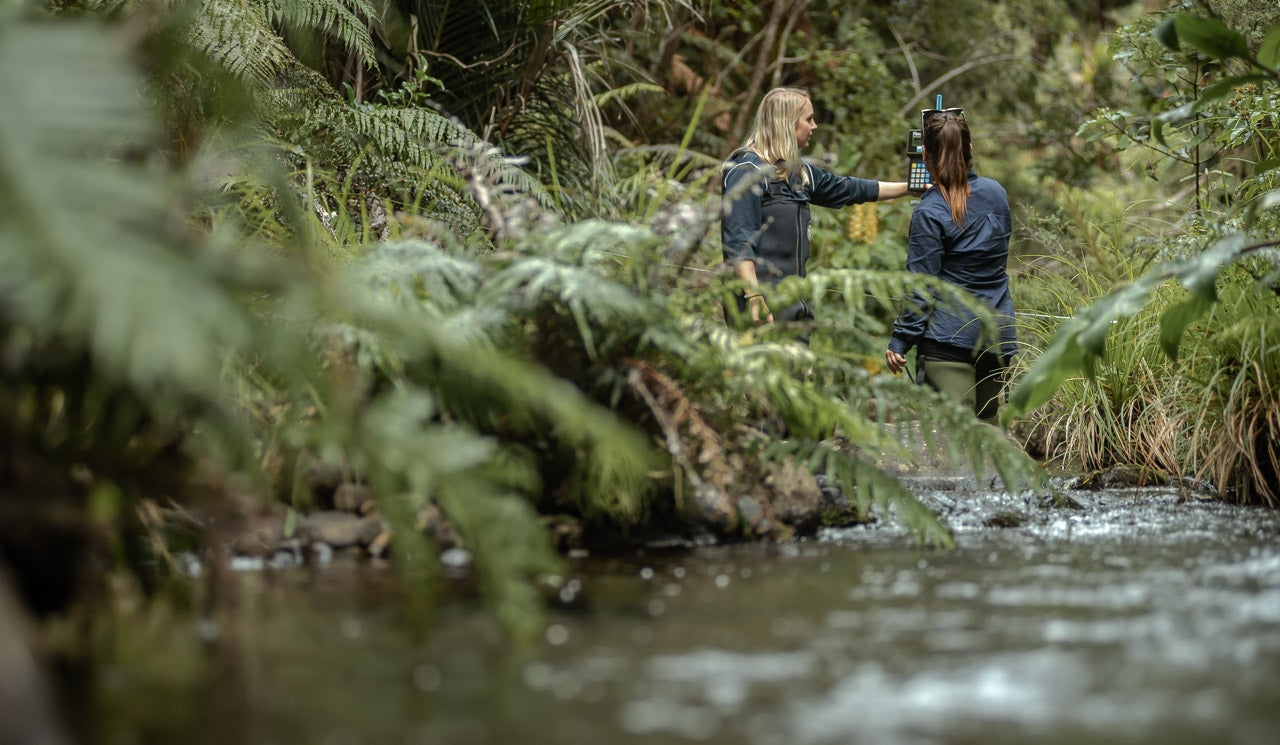 Watercare hydrologist Florence Mills and colleague take flow measurements in tributary stream in the Upper Huia dam.